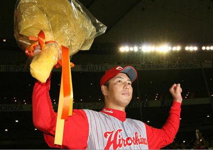 完投で100勝目を飾った黒田は花束を手に笑顔=東京ドーム